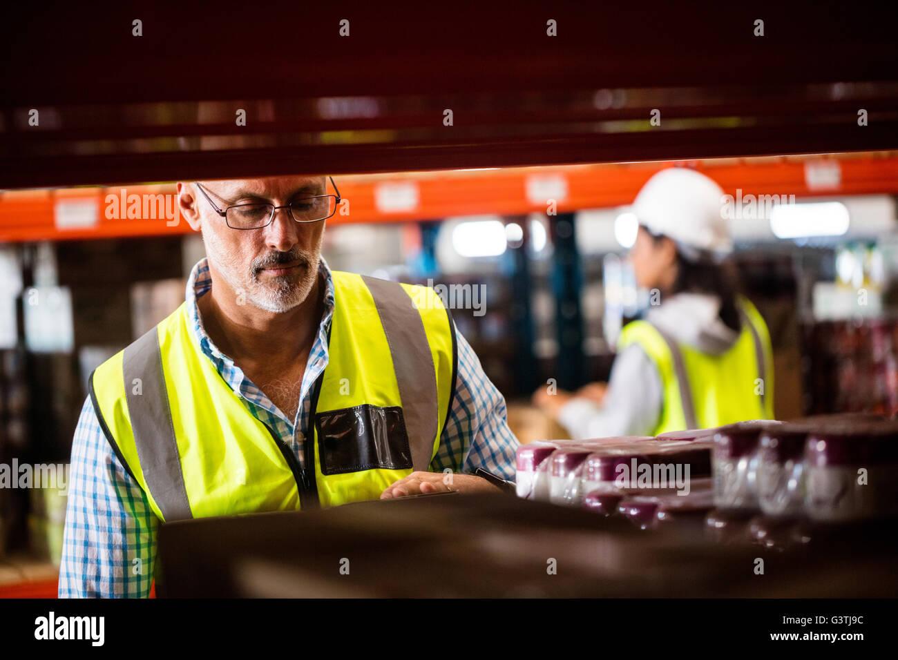 Les étagères de rangement d'entrepôt travailleurs Photo Stock