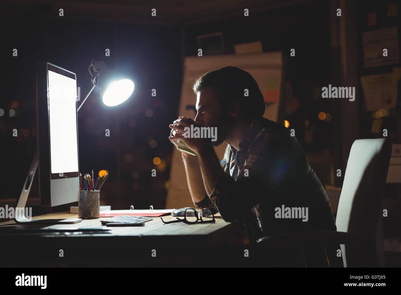 Businessman drinking coffee at night Photo Stock