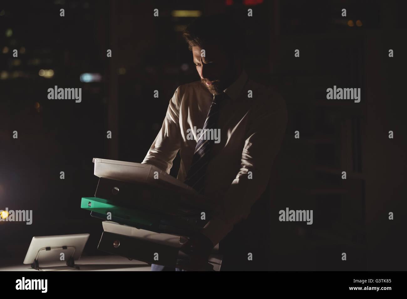 Businessman carrying folder dans la nuit Photo Stock