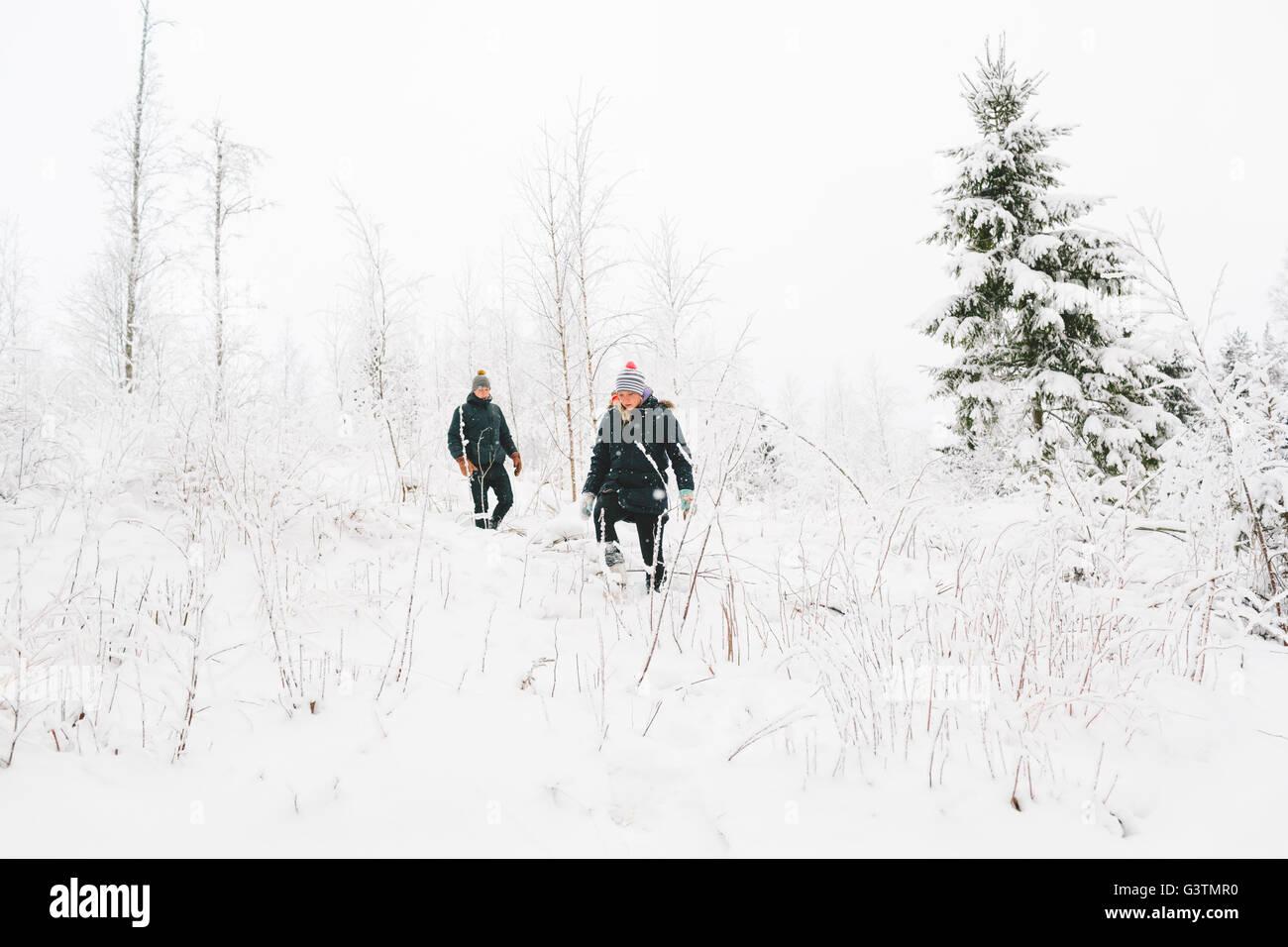 La Finlande, Jyvaskyla, Saakoski, jeune couple en train de marcher parmi les arbres nus en hiver Photo Stock