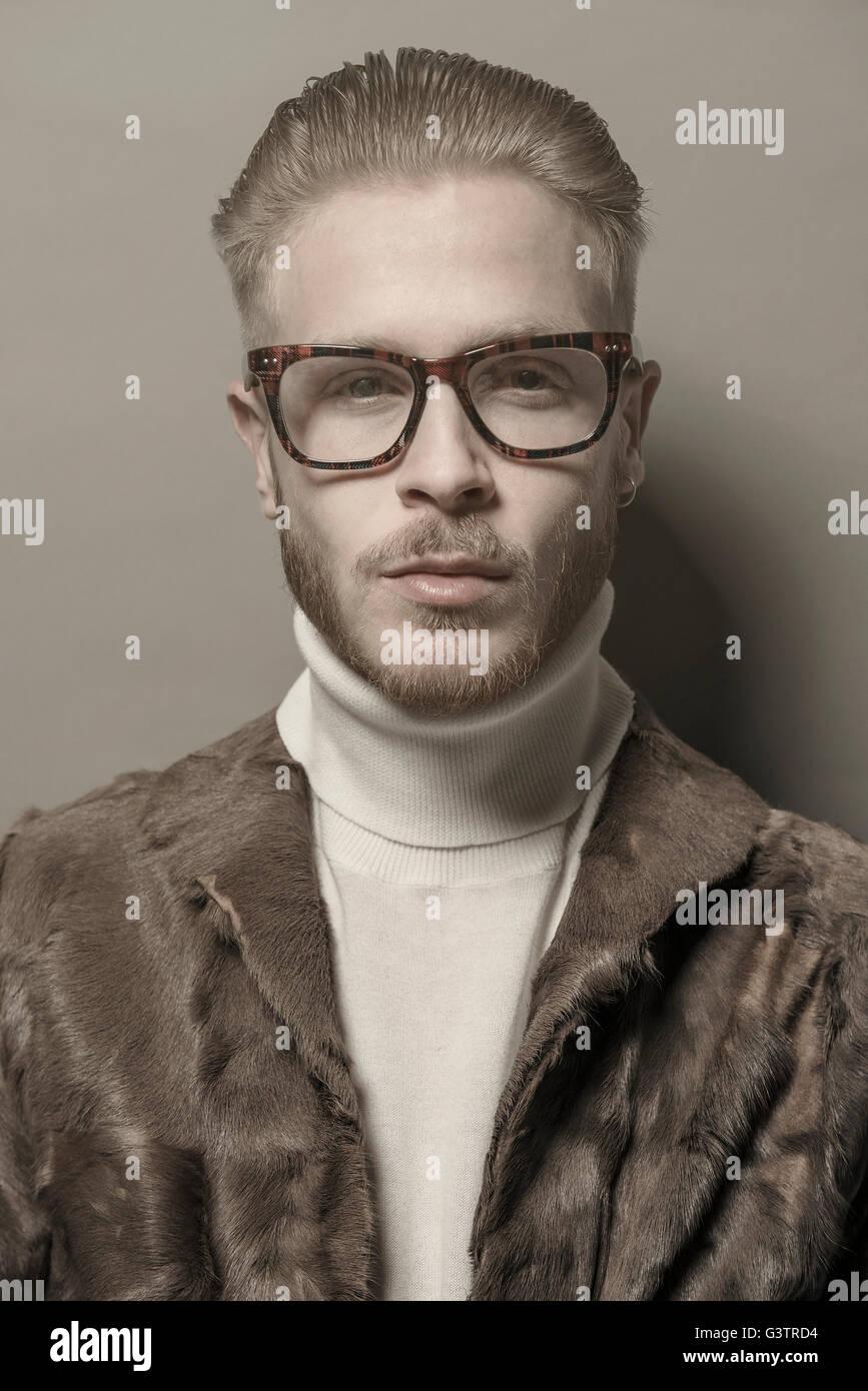 Studio portrait d'un jeune homme cool avec des lunettes portant un manteau de fourrure. Photo Stock