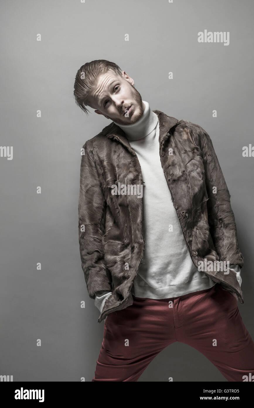Studio portrait d'un jeune homme cool portant un manteau de fourrure. Photo Stock
