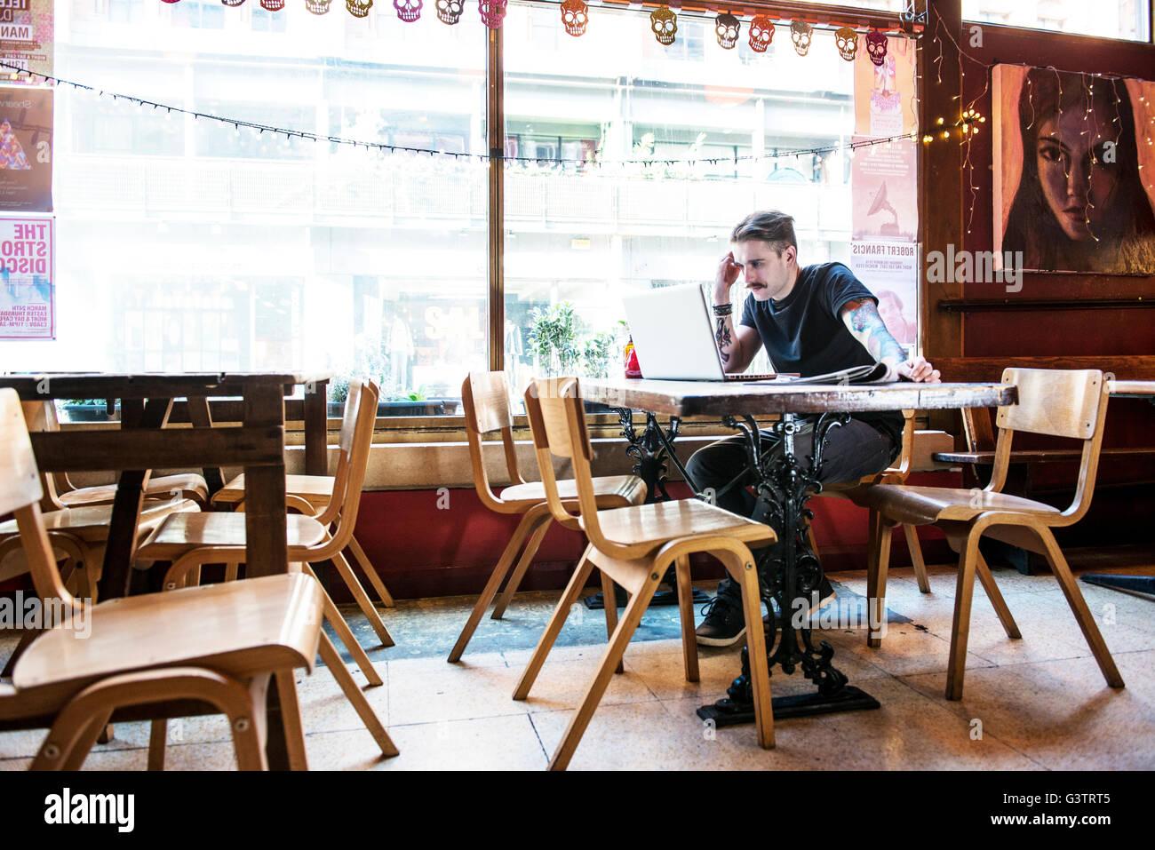 Un jeune homme assis à une table dans un café à Manchester. Photo Stock