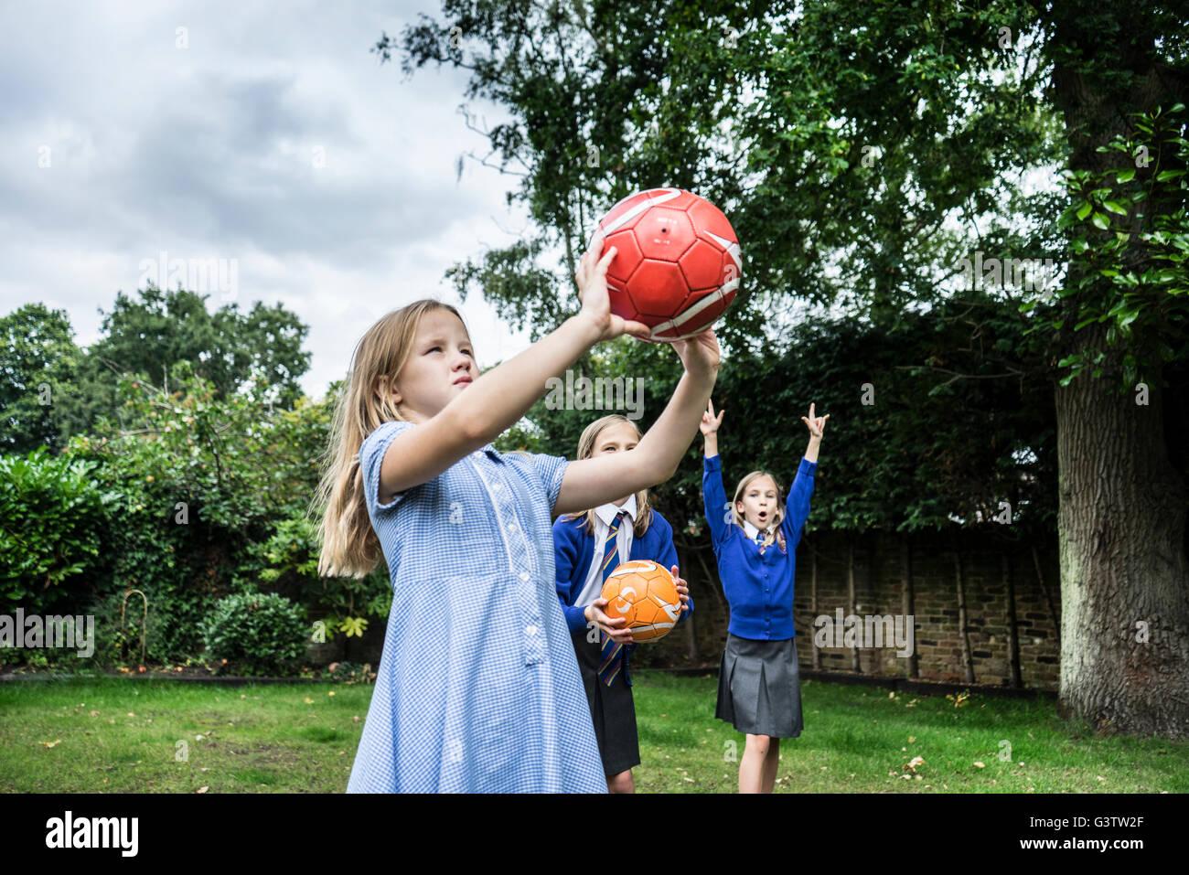 Trois jeunes filles en uniforme d'jouant avec des ballons de l'extérieur. Banque D'Images