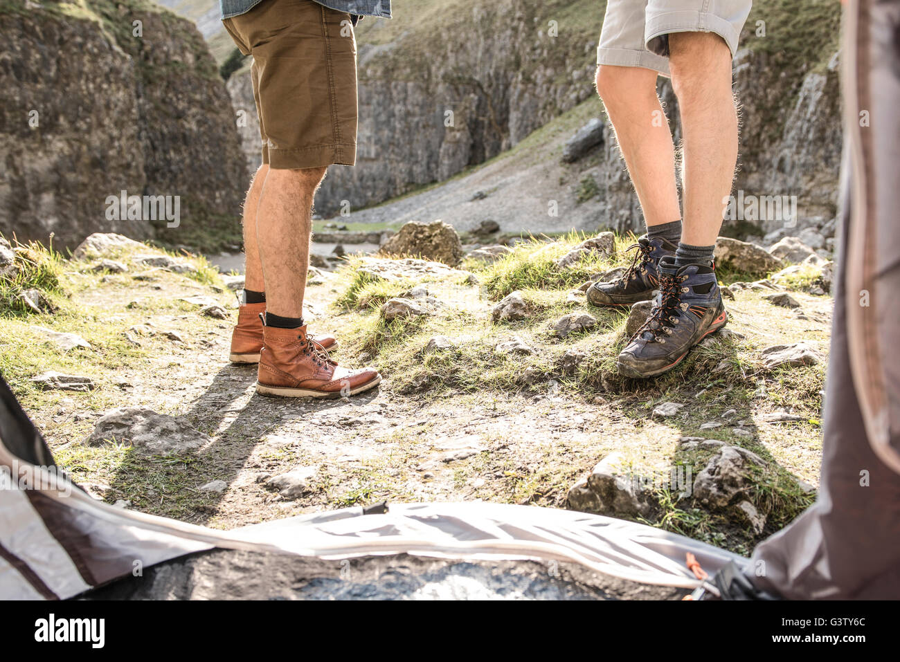 Les jambes de deux hommes vu de l'intérieur de leur tente dans un terrain accidenté. Photo Stock