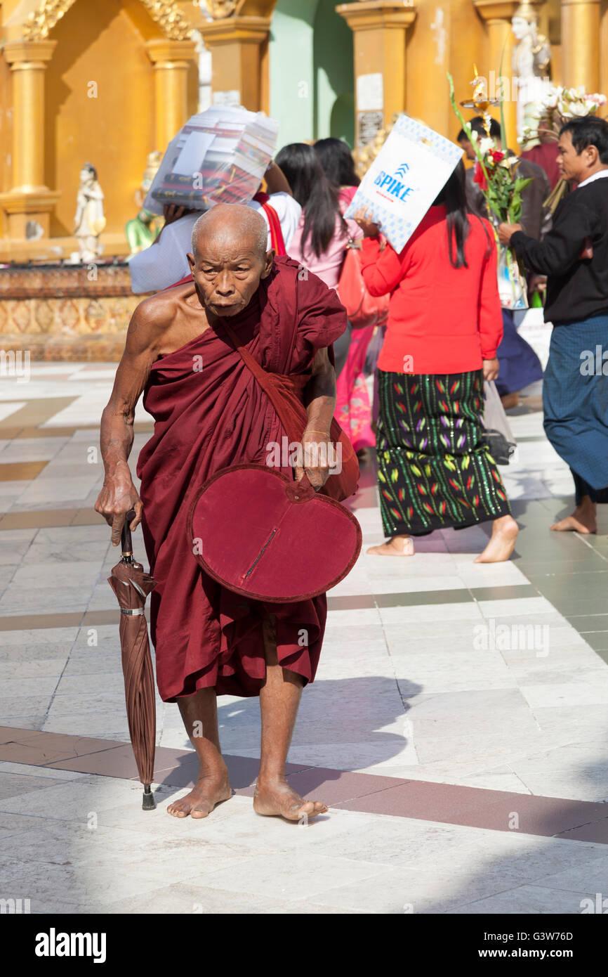 Un vieux moine courbé avec l'âge qui va effectuer sa dévotion à la Paya Shwedagon, à Photo Stock