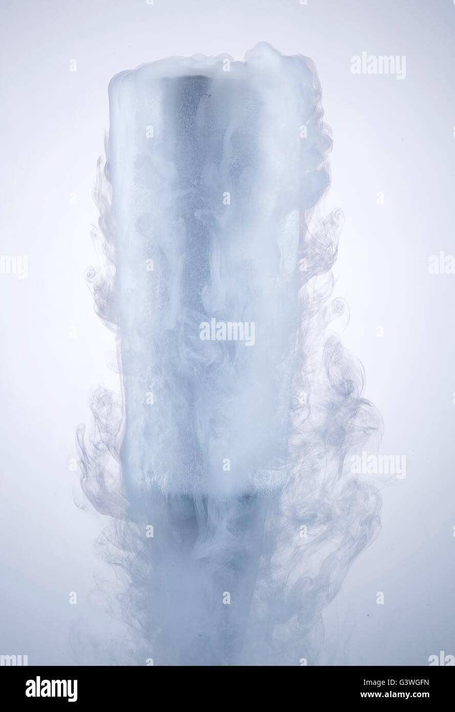 Verre avec de la glace sèche isolé sur un fond blanc. Photo Stock