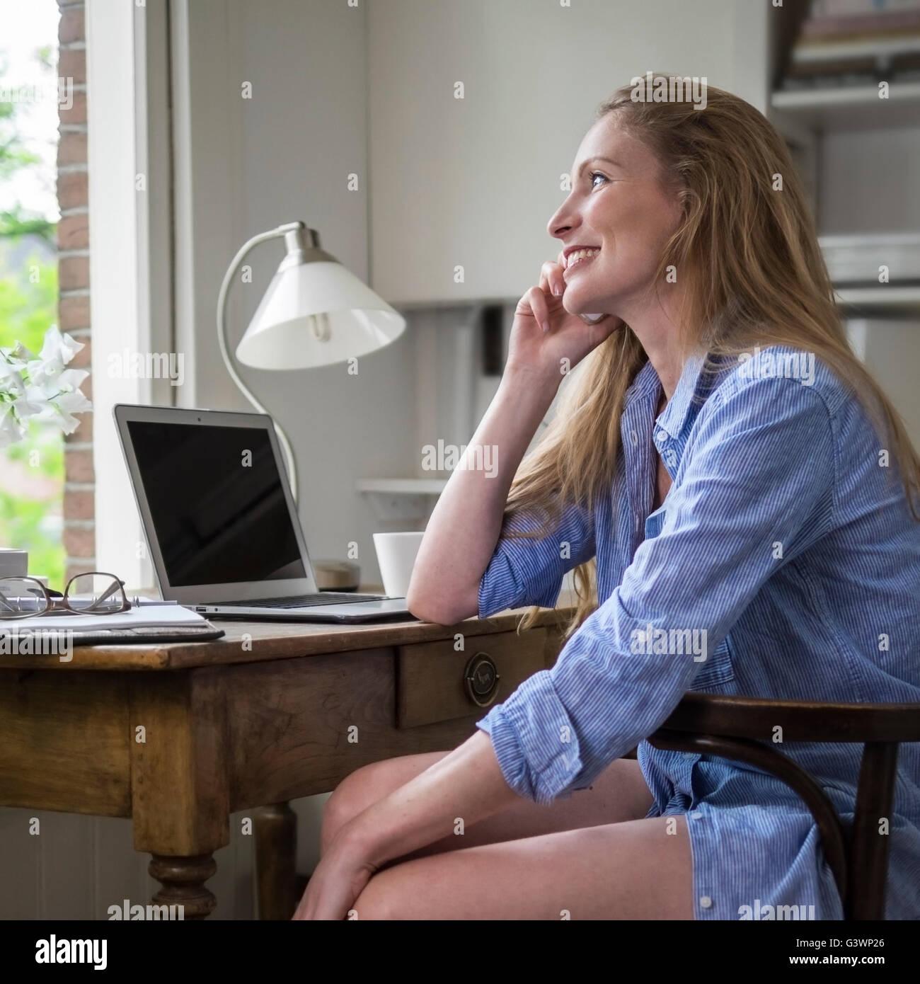Femme ayant un matin téléphone dans son bureau à domicile Photo Stock