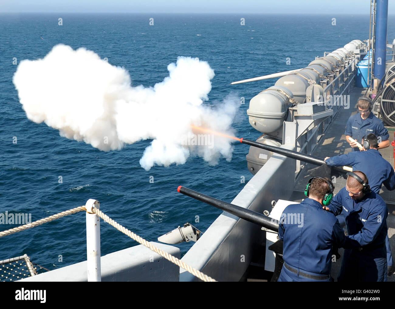 Gunner's mates essai au feu les canons à bord du navire USS Nimitz salut. Photo Stock