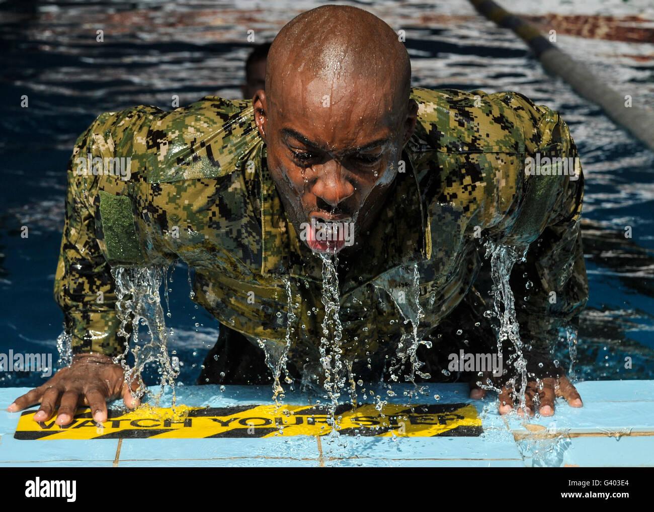 Soldat de la marine lui-même pousse hors de la piscine lors d'une course relais de nager. Banque D'Images