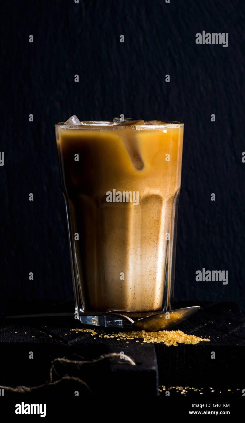 Café glacé avec du lait dans un grand verre, fond noir, selective focus Photo Stock