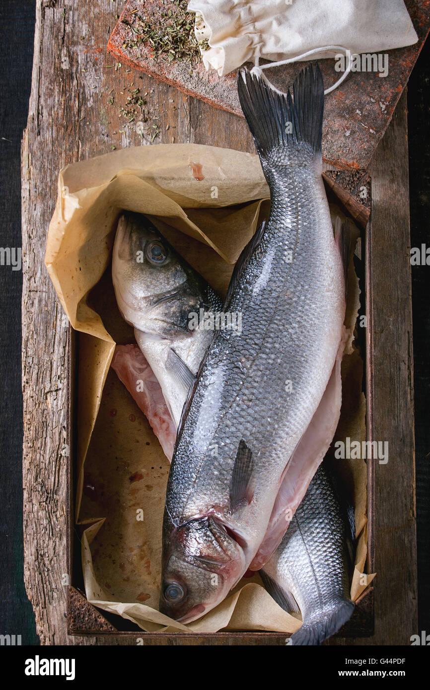 Deux poissons crus crus seebass dans boîte en bois avec des herbes sèches au fond de bois ancien. Vue Photo Stock