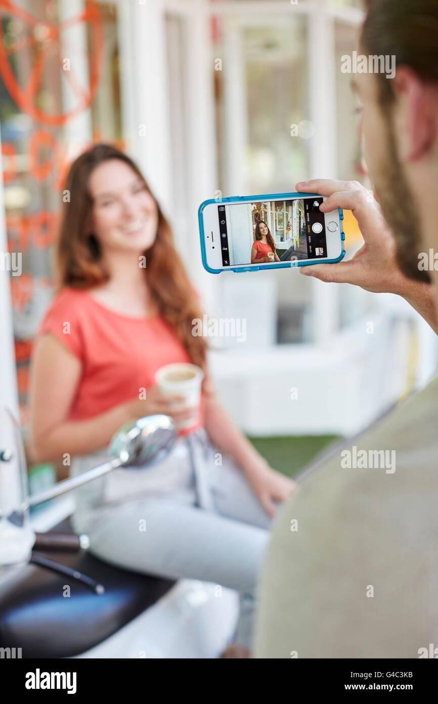 Parution du modèle. Personne prenant photo de jeune femme avec smartphone. Photo Stock