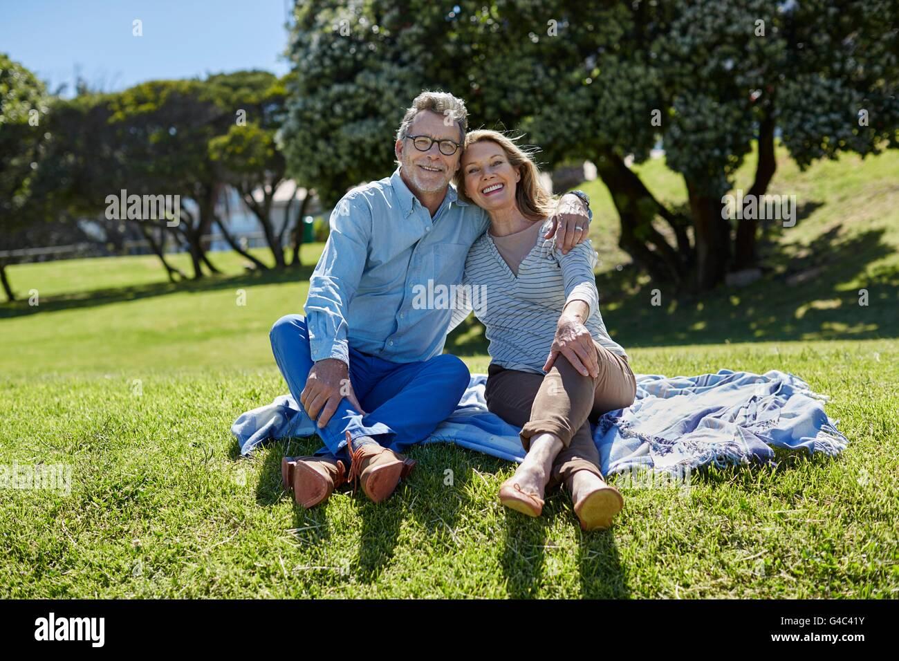 Parution du modèle. Senior couple on picnic blanket, bras autour de l'autre. Photo Stock