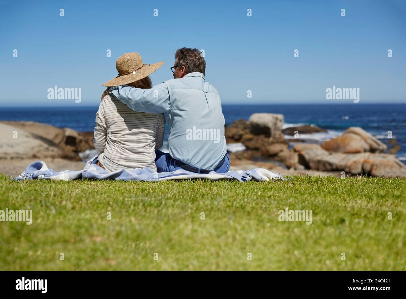 Parution du modèle. Senior couple on picnic blanket, l'homme avec le bras autour des épaules de la Photo Stock