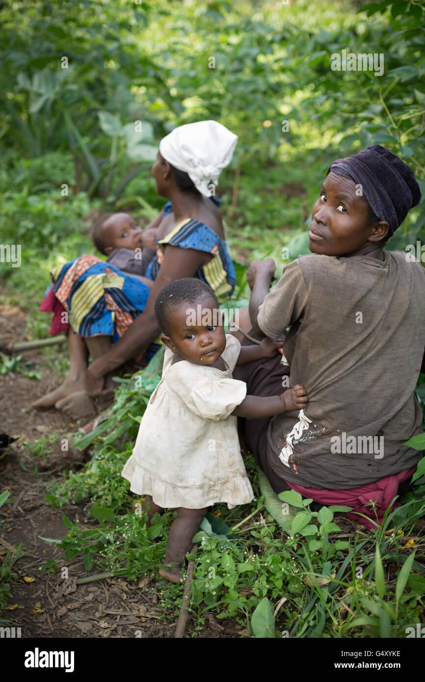 Les agricultrices reste dans l'ombre avec leurs enfants dans les régions rurales du district de Kasese, Photo Stock
