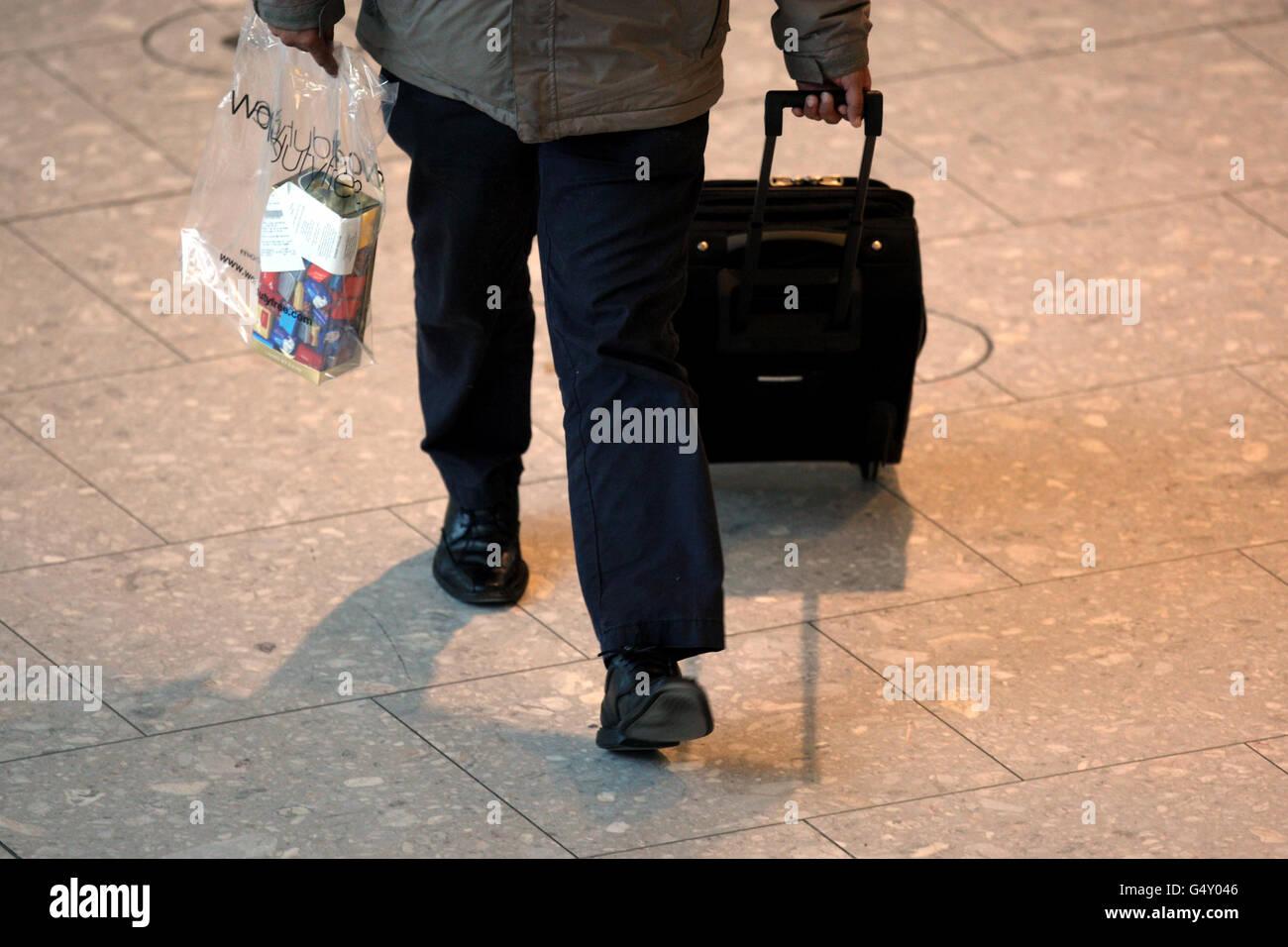 Un passager pousse ses bagages dans le terminal 5 de Heathrow Aéroport Banque D'Images