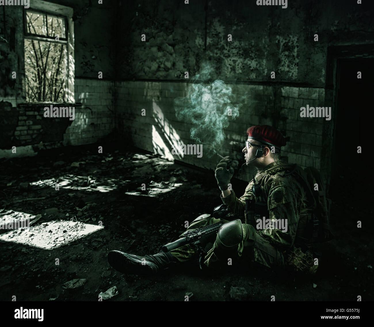 Soldat fatigué. guerre portant un uniforme militaire avec de rapides automatique assis dans la nuit dans le Photo Stock