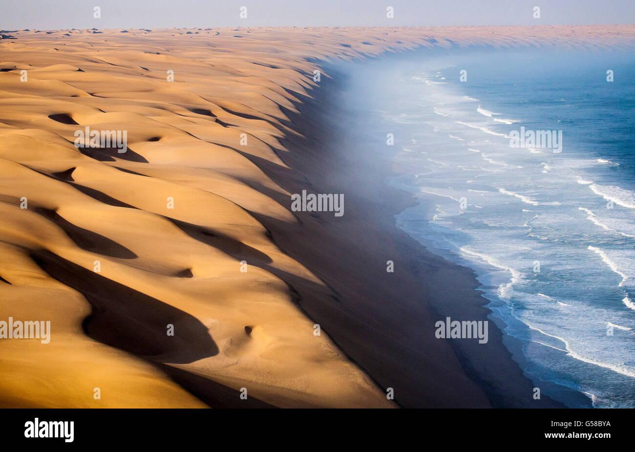 Les vagues de l'océan Atlantique l'avance vers les dunes de sable du désert du Namib Namibie Afrique du Sud Banque D'Images