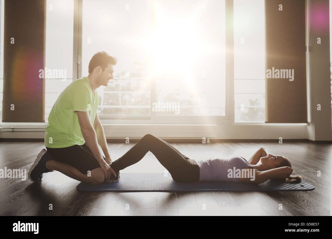 Femme avec un entraîneur personnel faisant asseoir ups in gym Photo Stock