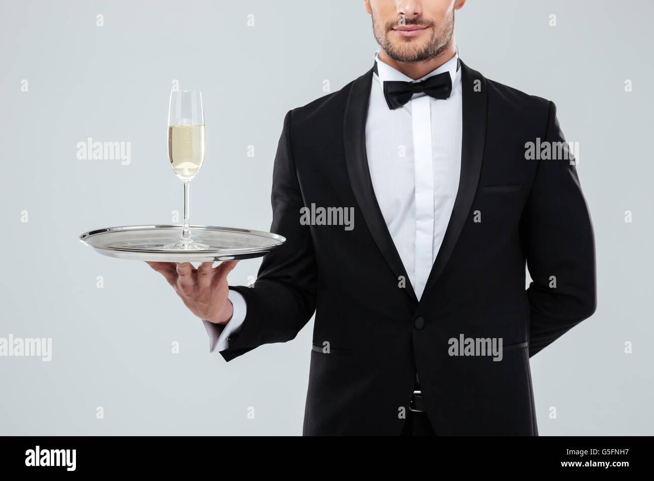 Beau jeune garçon en smoking et noeud papillon debout et tenant le bac avec un verre de champagne Banque D'Images