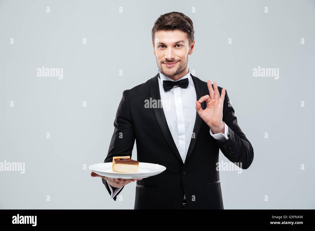 Beau jeune garçon en smoking avec nœud papillon maintenant la plaque avec du gâteau et montrant ok sign Banque D'Images