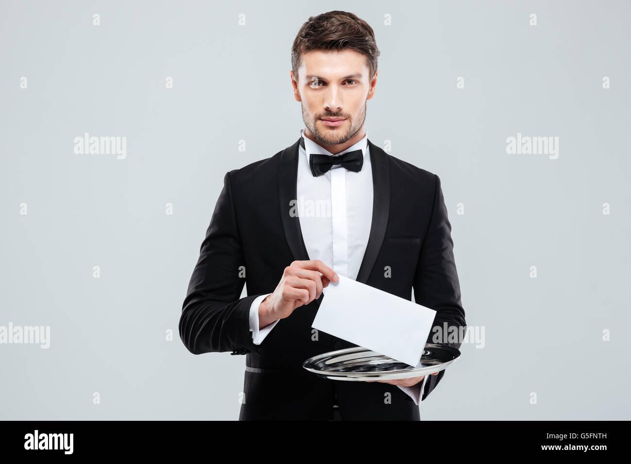 Beau jeune garçon in tuxedo holding tray with carte vierge Banque D'Images