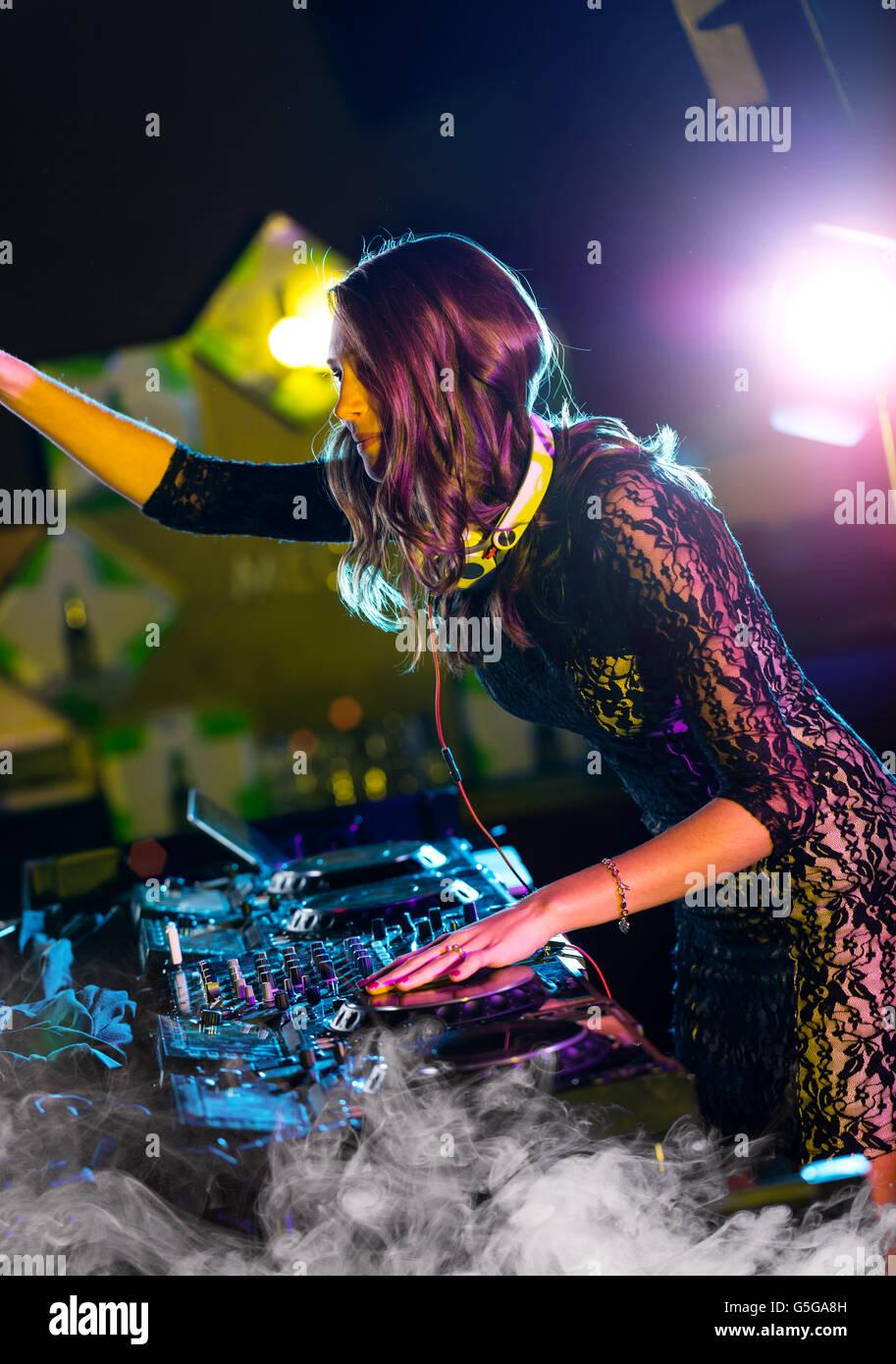Disc Jockey fille brune mélangeant musique électronique en club Photo Stock