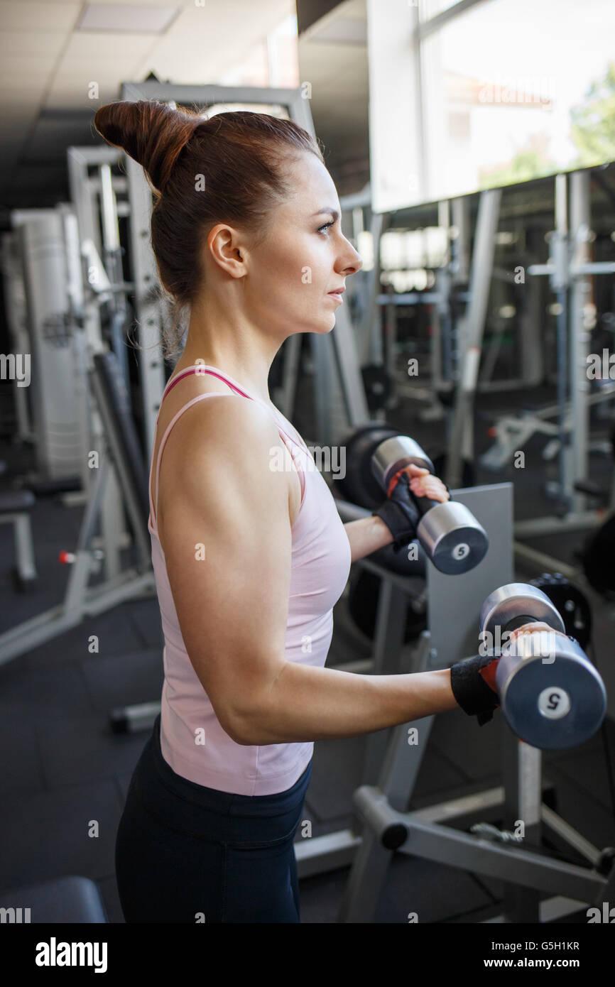 Jeune femme confiante biceps faisant de l exercice avec haltères en centre  de remise en forme. Formation fille Slim dans le sport avec haltères 593390ffc20