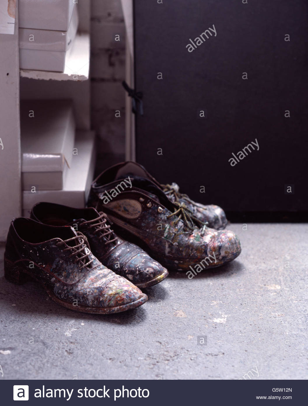 Deux paires de chaussures éclaboussés de peinture dans un atelier d'artiste Photo Stock