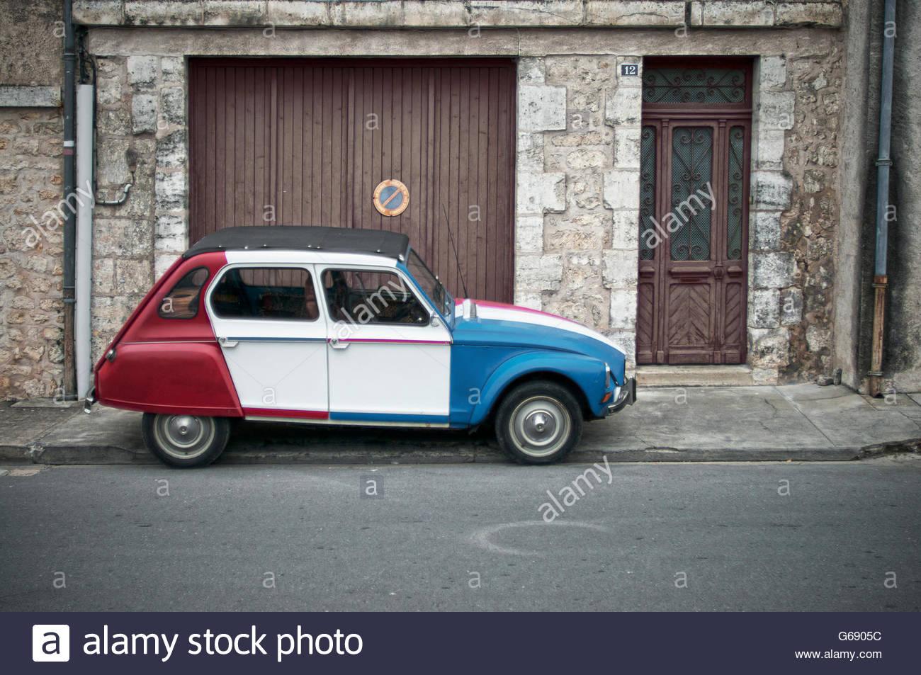 Profil de côté vintage 2CV Citroën peinte en rouge, blanc et bleu. Photo Stock