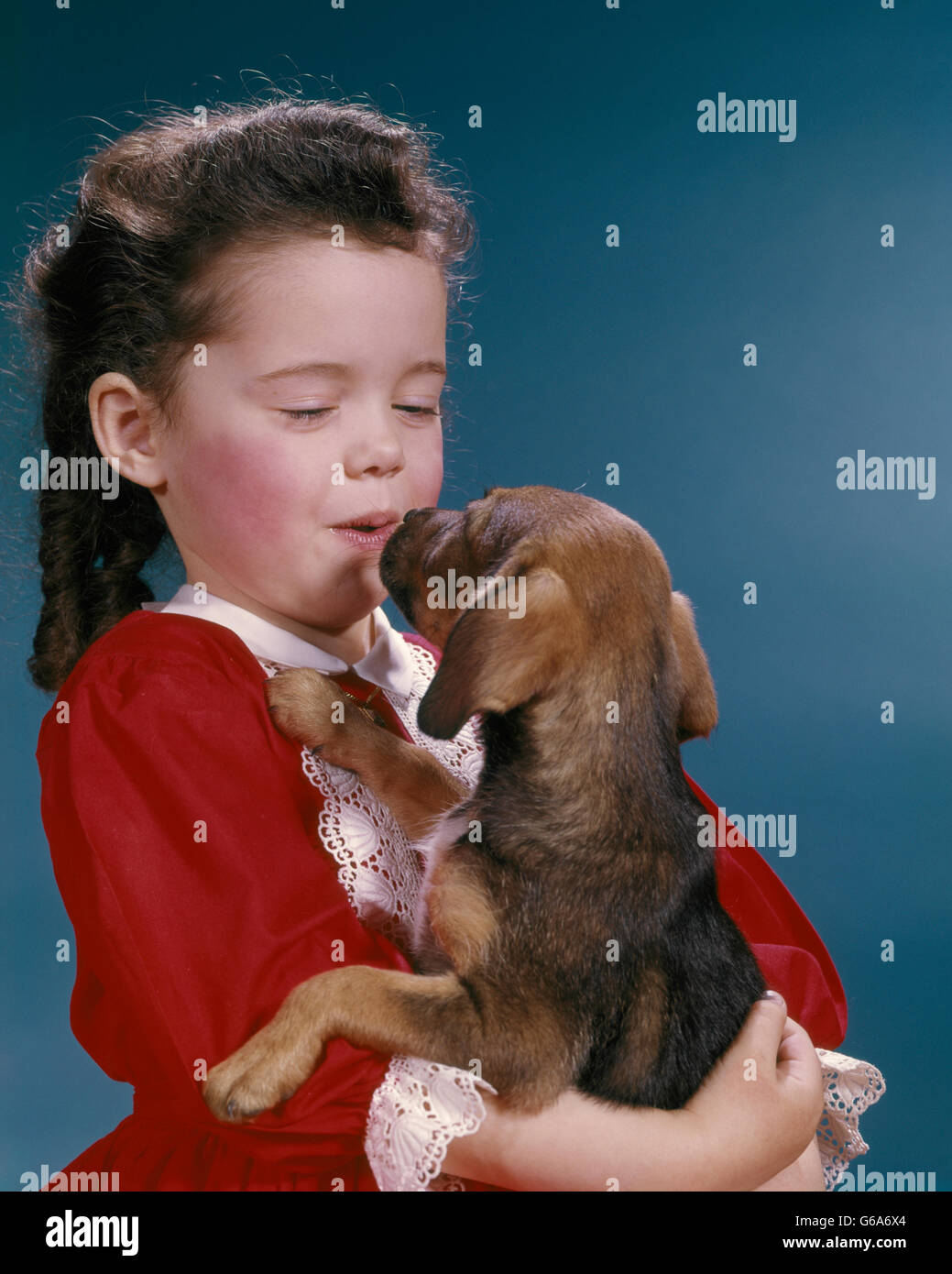 1960 LITTLE GIRL KISSING HER BEAGLE PUPPY Photo Stock