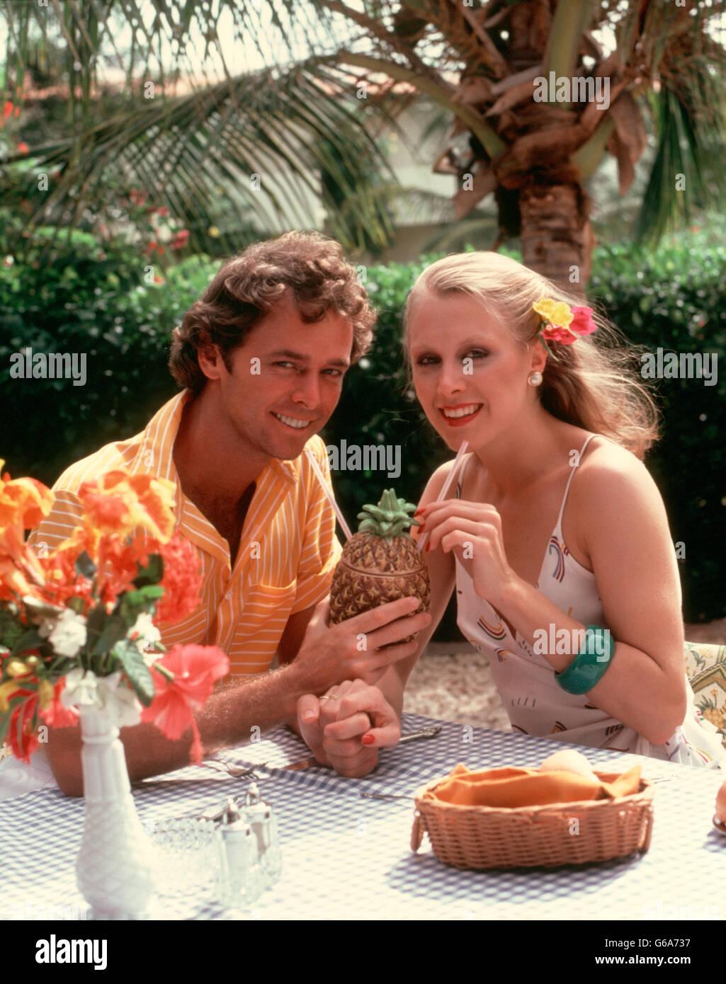 1980 SMILING COUPLE DRINKING COCKTAIL HORS D'UN VERRE EN FORME D'ANANAS TROPICAL EN CAFE Photo Stock