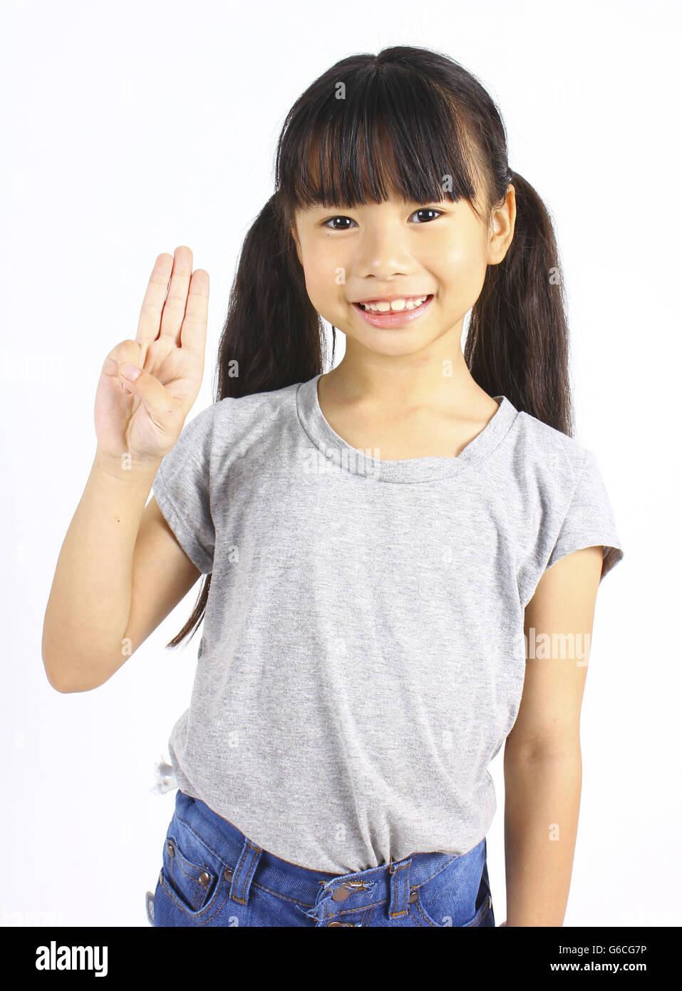 Portrait de jeune fille mignonne avec trois doigts isolated on white Photo Stock