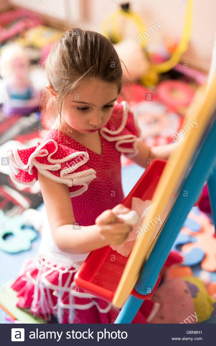 Petite fille dessin sur tableau dans la chambre des enfants Photo Stock