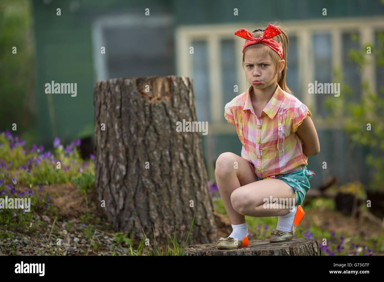 Petite fille dans une mauvaise humeur assis près de la maison du village. Photo Stock