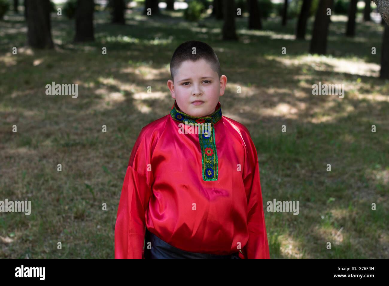 Le garçon dans la chemise russe contre le bois Photo Stock