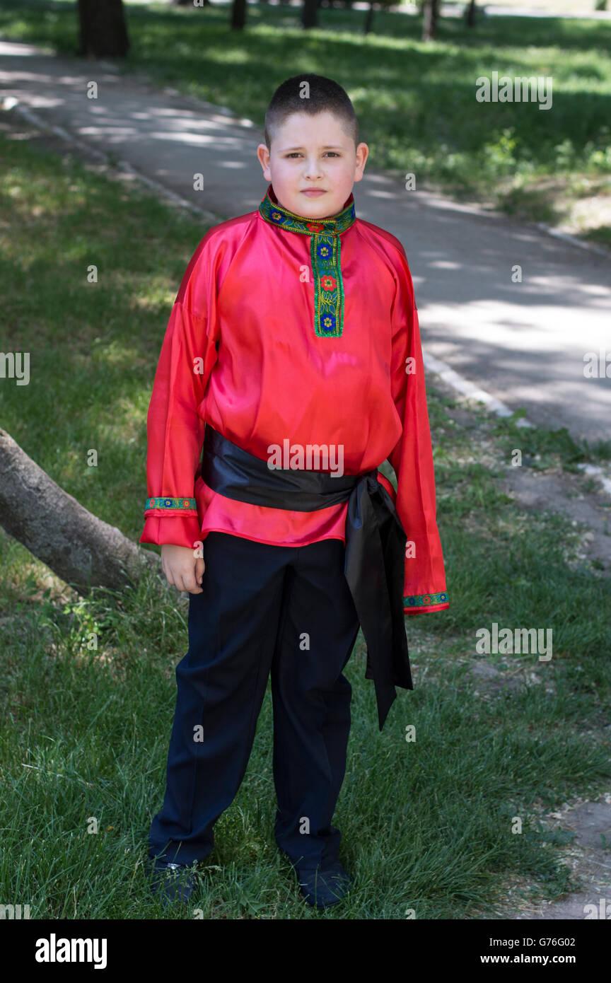 Le garçon dans la chemise rouge russe contre park Photo Stock