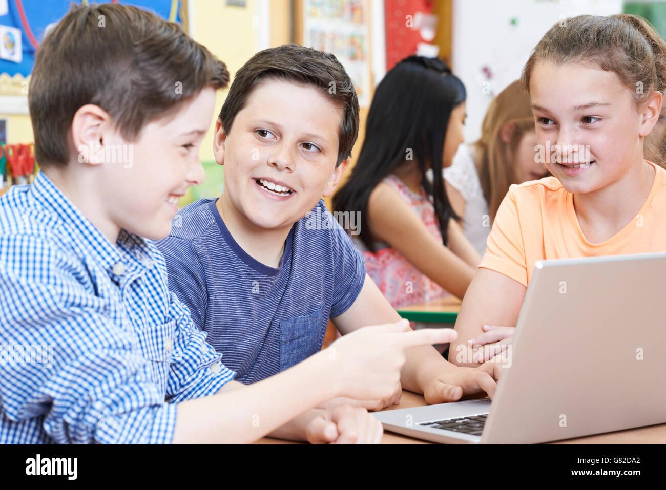 Groupe d'enfants de l'école primaire travaillant ensemble in Computer Class Photo Stock