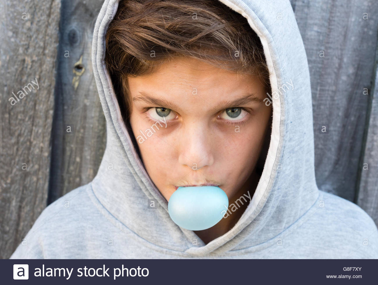 Portrait of teenage boy agressif avec hoodie blowing bubble gum contre la clôture en bois gris Photo Stock