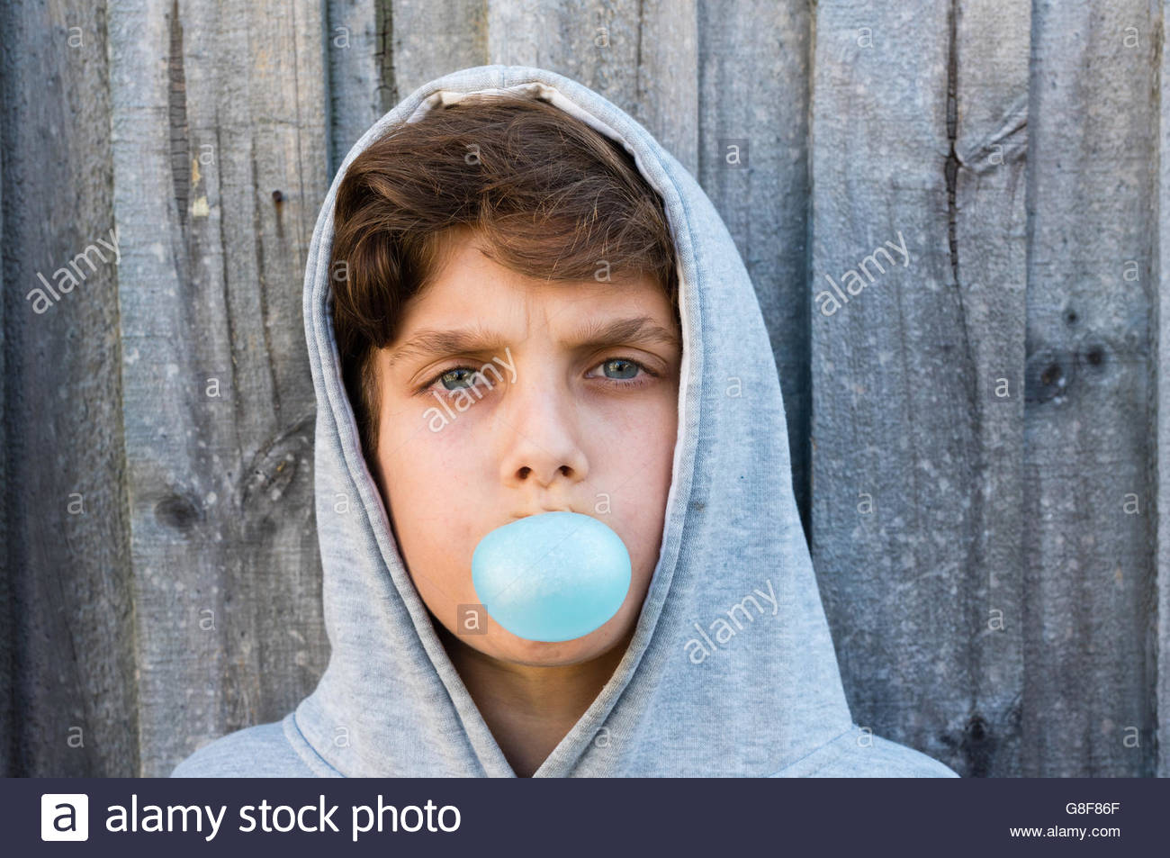 Head shot of woman blowing bubble gum bleu contre une clôture en bois gris Photo Stock