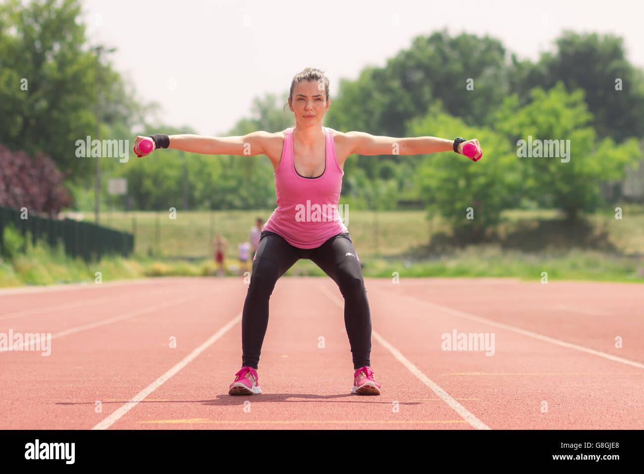 Athlète fille poids squat rouge d'une piste de course Photo Stock