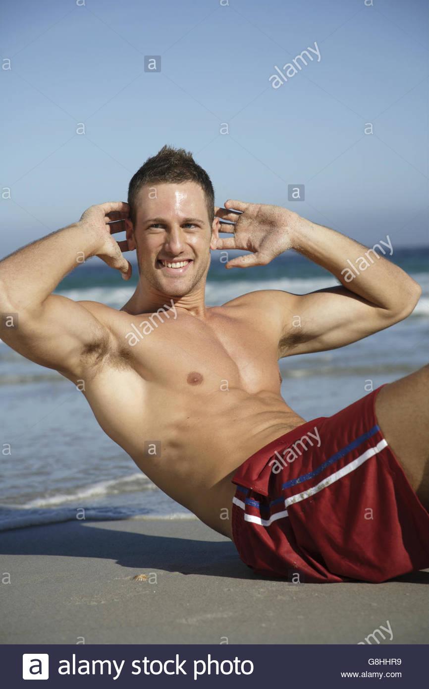 Man doing sit-ups at beach Photo Stock