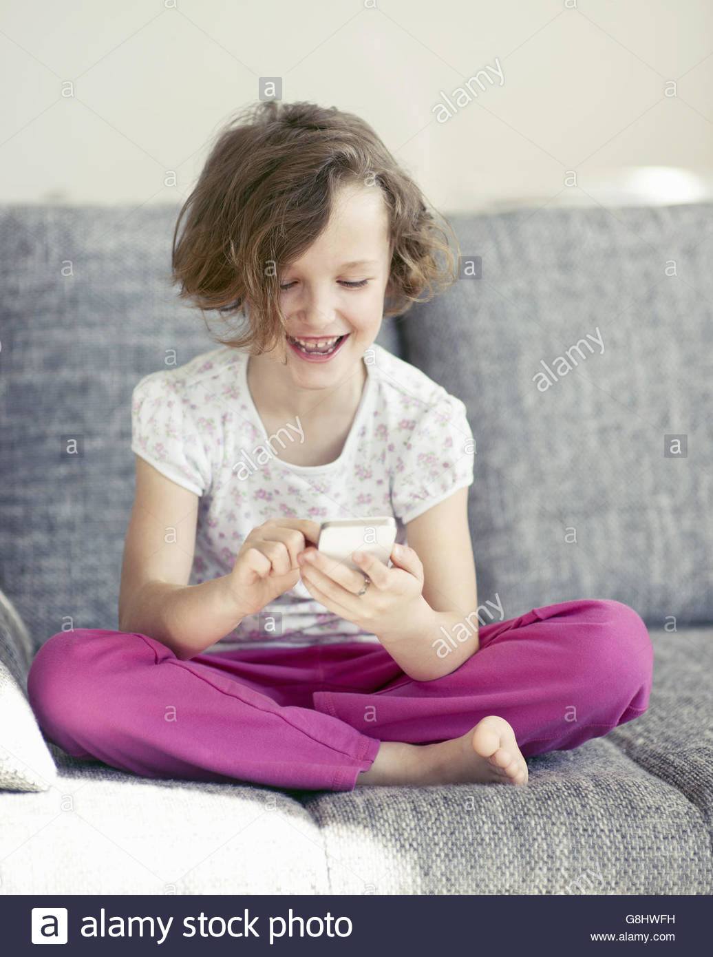 Young Girl using cellphone sur canapé Photo Stock