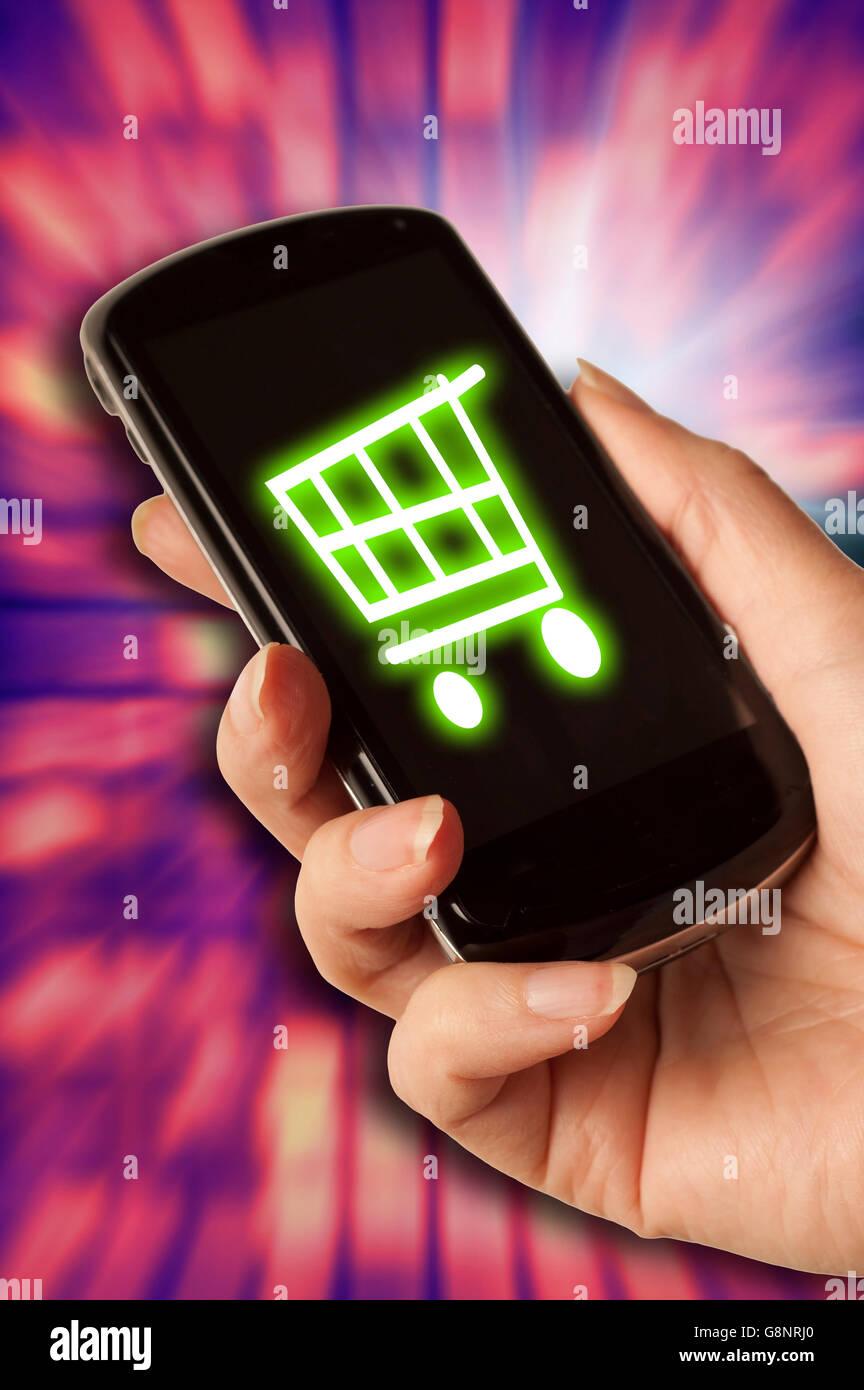 Femme main tenant un téléphone cellulaire avec une icône du panier à l'écran, en ligne Photo Stock