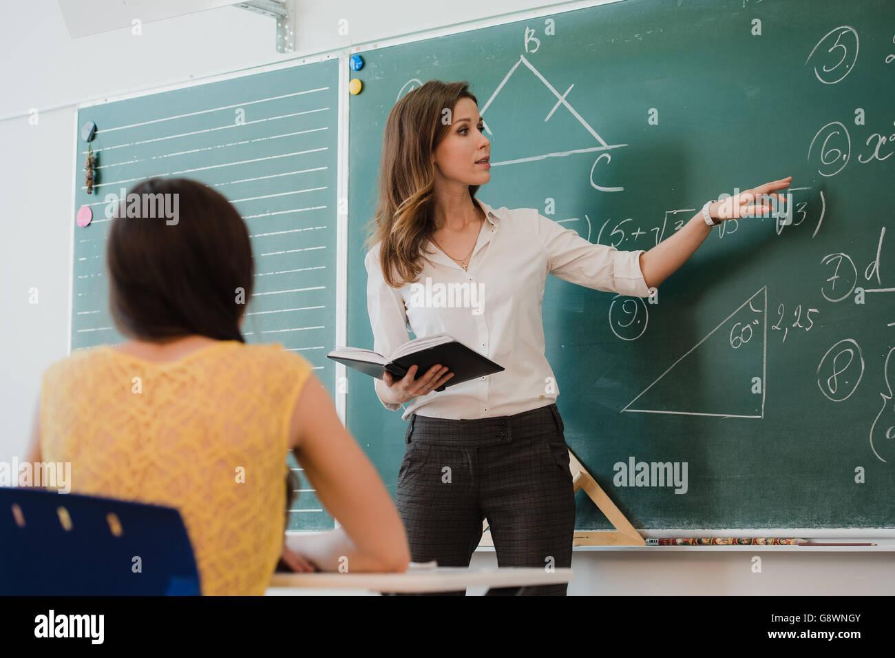 Enseignant ou éducateur ou causeries de donner de leçon devant un tableau noir ou d'une feuille de Photo Stock