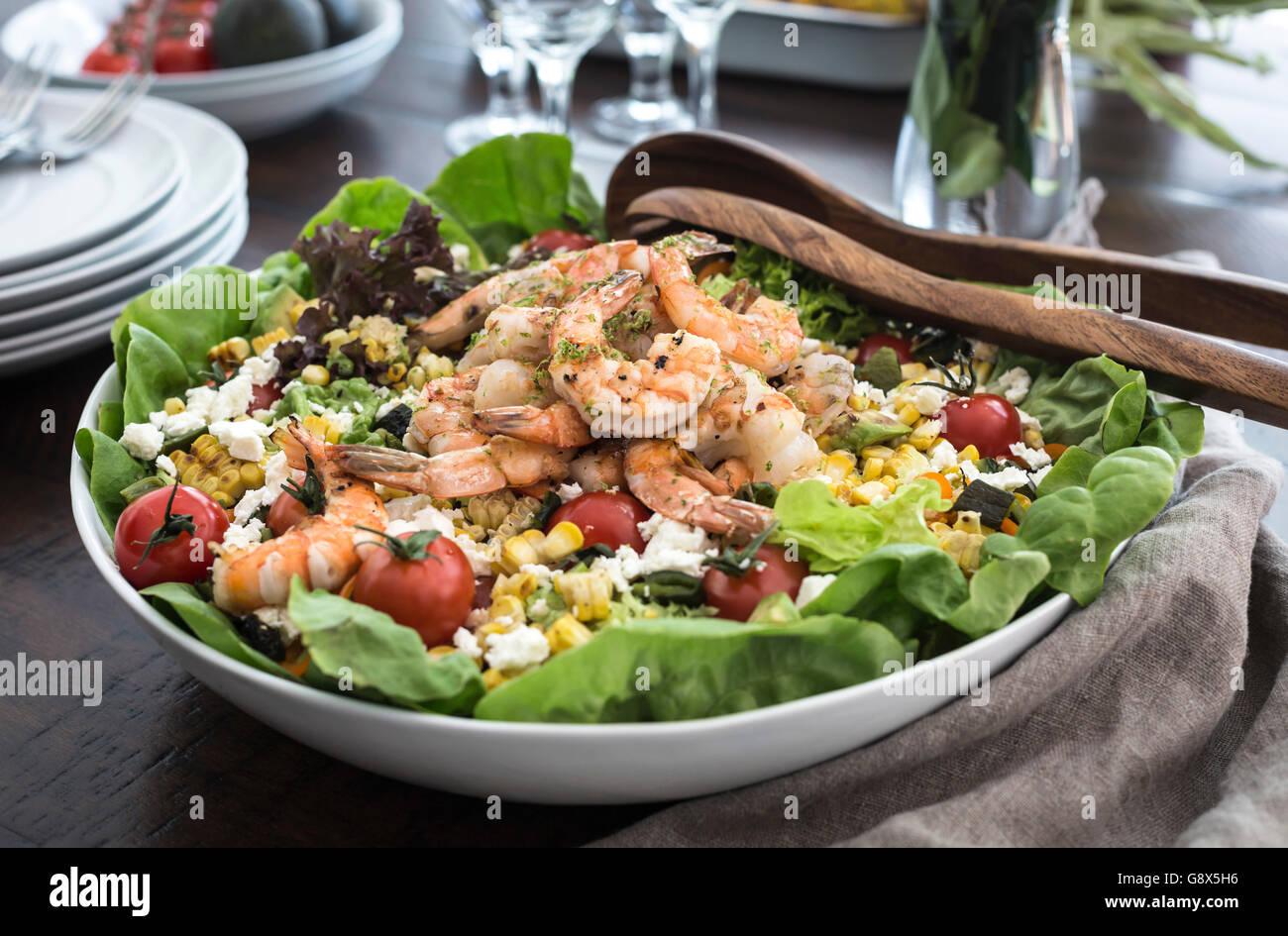 Un grand bol de crevettes grillées et salade de maïs est photographié à partir de la vue de Photo Stock