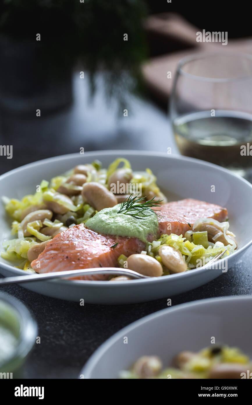 Une assiette pleine de haricots beurre blanc garni de tranches de saumon cuit au four est photographié à Photo Stock