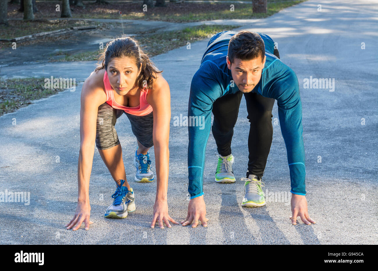 Young Hispanic couple espagnol de ligne de départ l'exécution de la concurrence concours gagnant tendue Photo Stock
