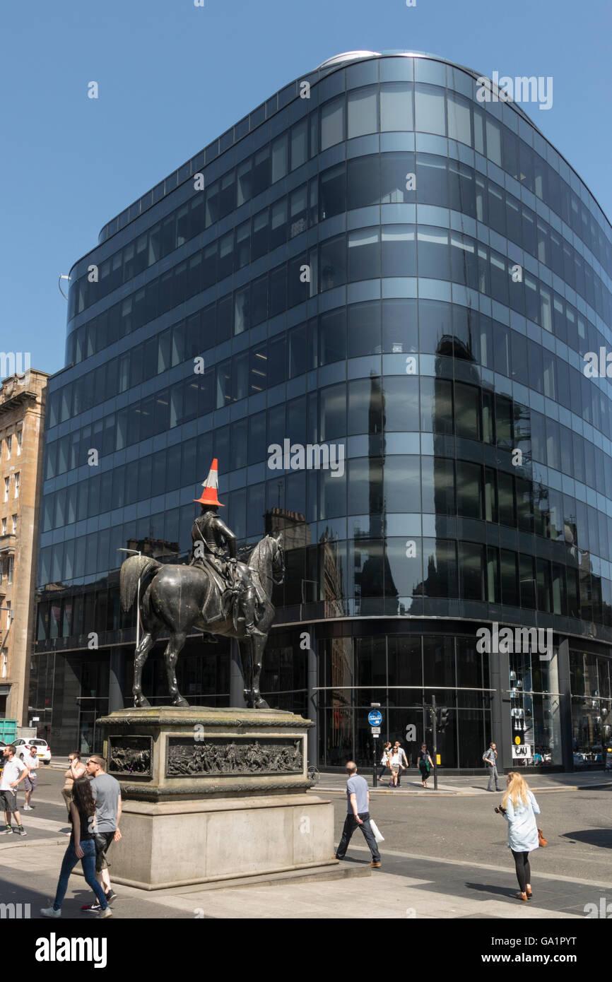 Statue du duc de Wellington avec circulation cône sur la tête, contre l'immeuble de bureaux moderne, Glasgow, Écosse, Royaume-Uni, Banque D'Images